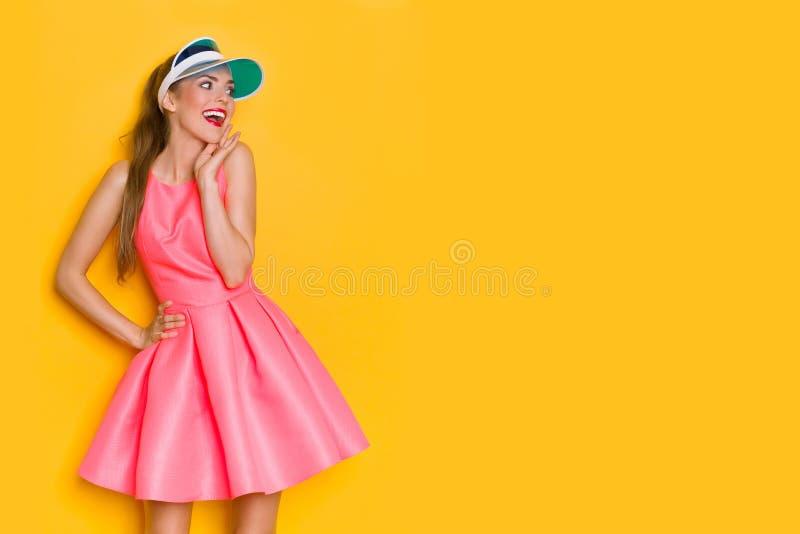 桃红色套衫连超短裙的激动的年轻女人看和笑 库存照片