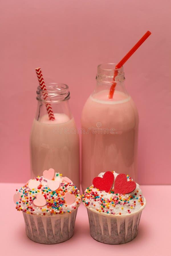 桃红色奶昔瓶和杯形蛋糕 免版税库存图片