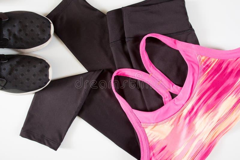 桃红色妇女的体育胸罩黑色体育气喘和黑体育鞋子 图库摄影