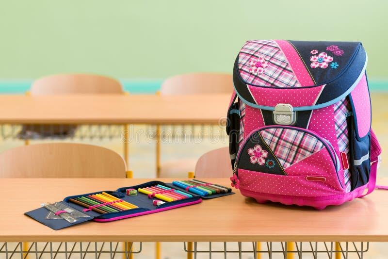 桃红色娘儿们书包和笔匣在一张书桌上在一间空的教室 日第一所学校 免版税库存图片