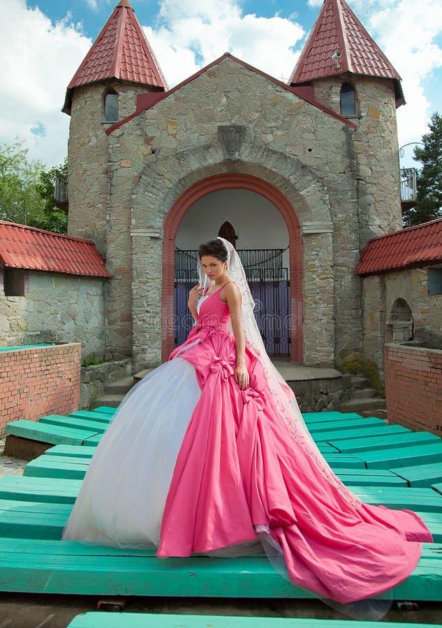 桃红色婚礼礼服的新娘 免版税库存图片