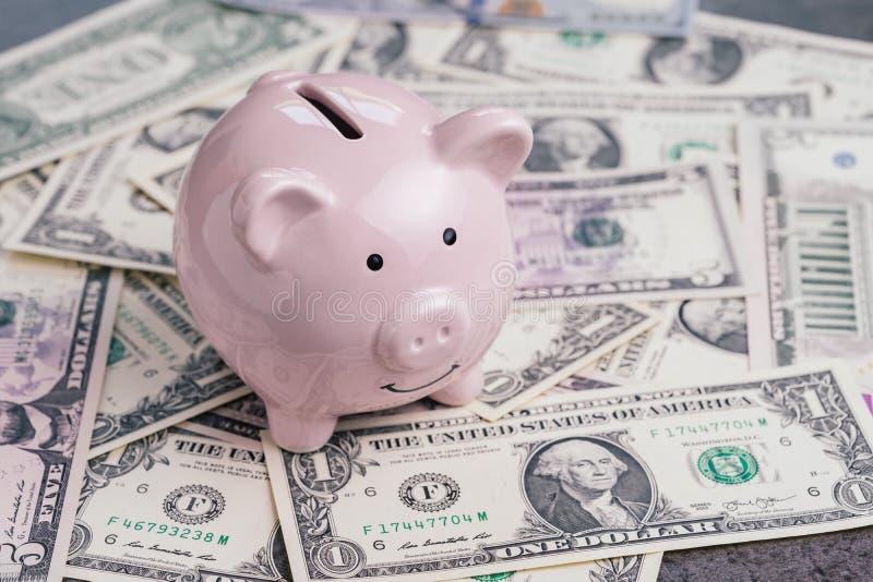 桃红色存钱罐或硬币银行堆的美元钞票金钱、投资成长、财政背景或者挽救储蓄 库存图片