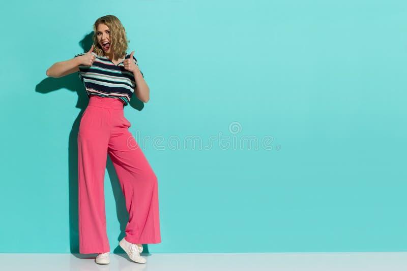 桃红色宽腿长裤、运动鞋和镶边女衬衫的时髦的妇女显示赞许 免版税库存图片