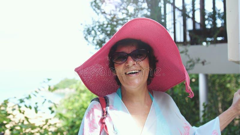 桃红色帽子和太阳镜的愉快的成熟妇女在假期的热带手段 免版税库存图片