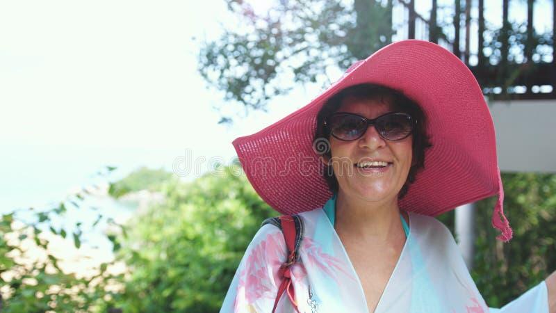 桃红色帽子和太阳镜的愉快的成熟妇女在假期的热带手段 库存照片
