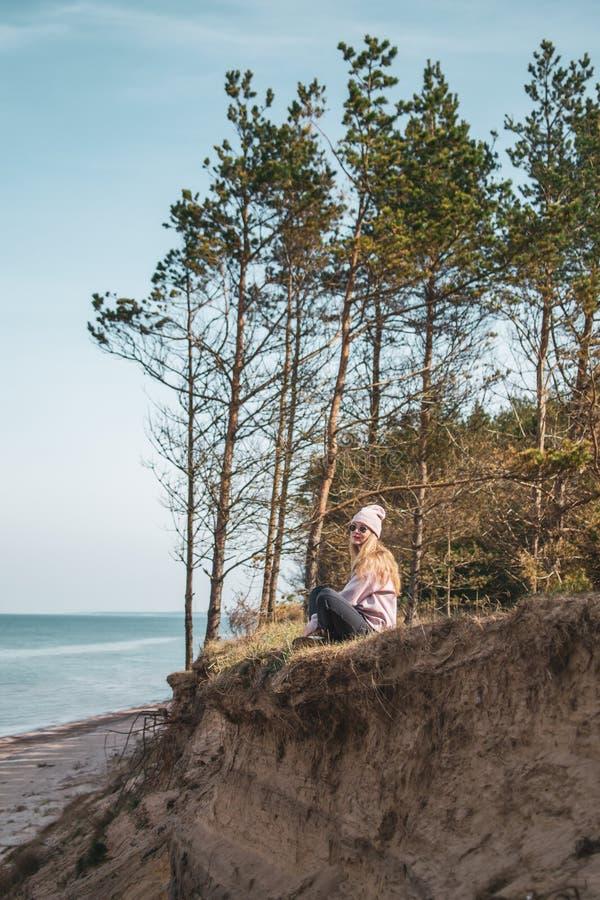 桃红色帽子的年轻妇女单独坐虚张声势,看海,自由概念,平安的大气 免版税图库摄影