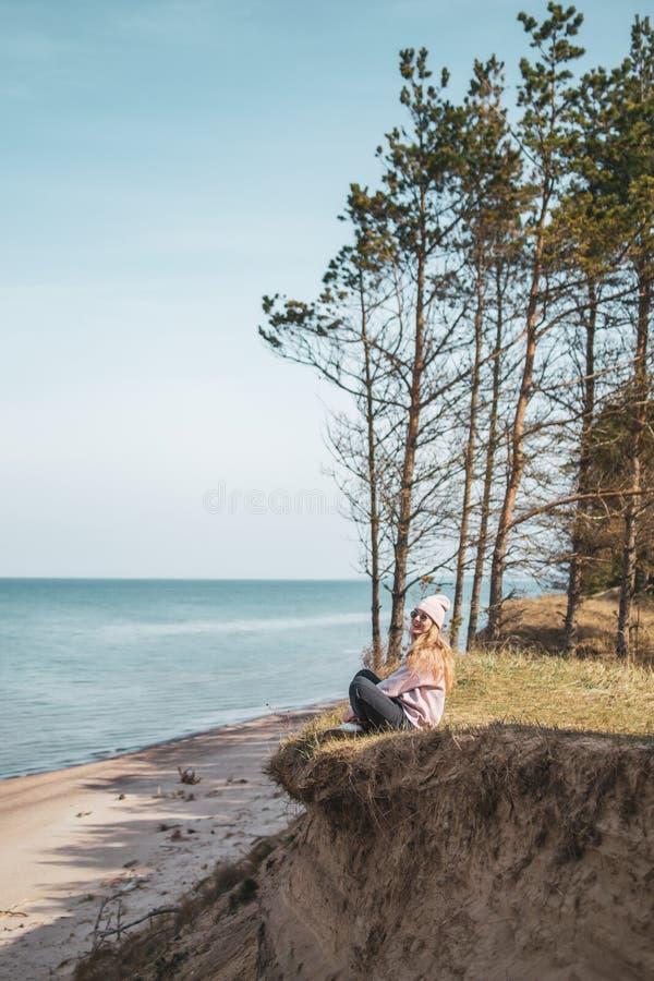 桃红色帽子的年轻妇女单独坐虚张声势,看海,自由概念,平安的大气 免版税库存图片