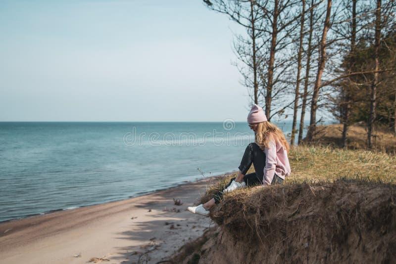 桃红色帽子的年轻妇女单独坐虚张声势,看海,自由概念,平安的大气 免版税库存照片