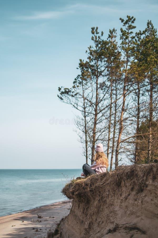 桃红色帽子的年轻妇女单独坐虚张声势,看海,自由概念,平安的大气 库存照片