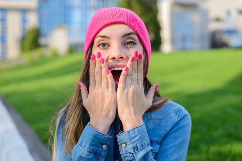 桃红色帽子的愉快的快乐的惊奇的十几岁的女孩,有桃红色钉子的 库存照片