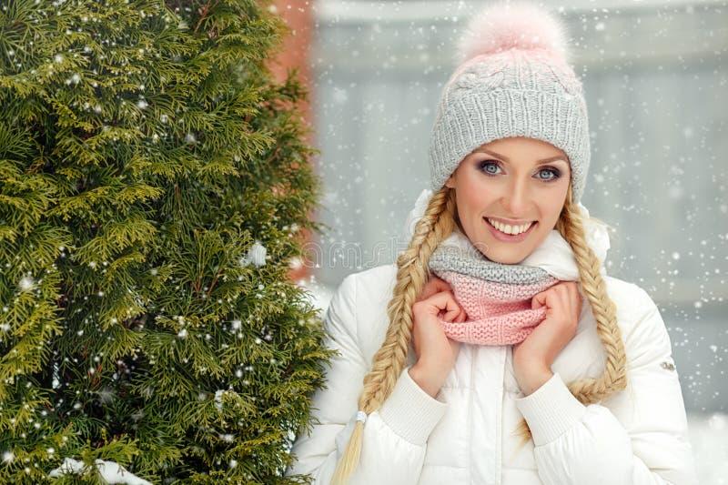桃红色帽子的白肤金发的女孩广泛地微笑在冬天的 免版税库存图片