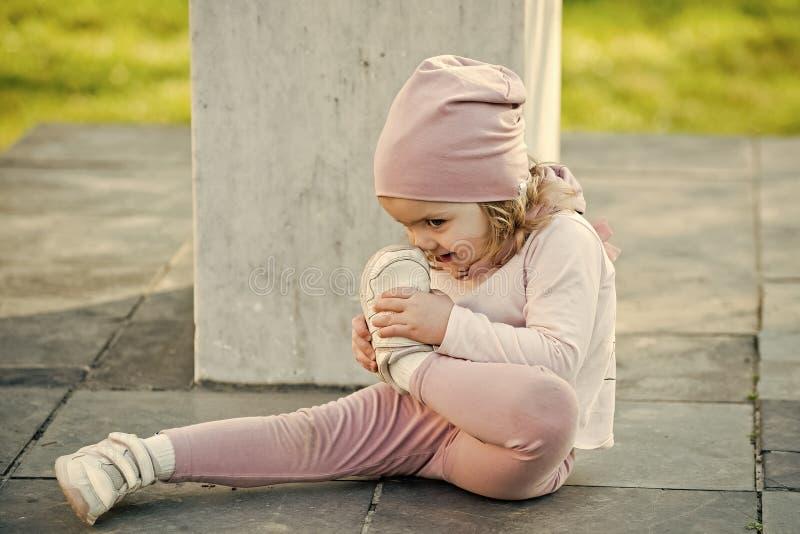 桃红色帽子的,衣裳女孩接触与体育鞋子的鼻子 库存照片