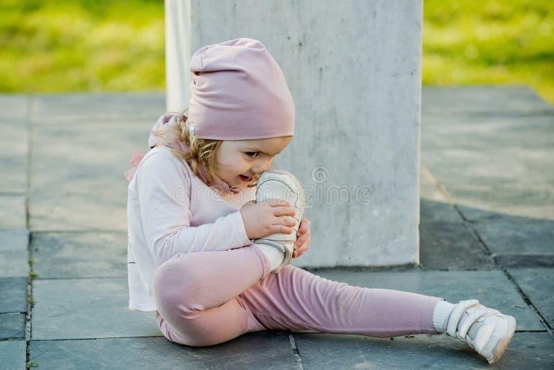 桃红色帽子的,衣裳女孩接触与体育鞋子的鼻子 图库摄影