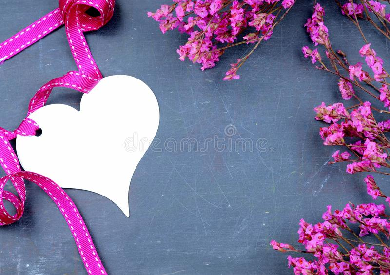 桃红色干花的春天图象在板岩背景的与白色心形和配比的丝带有益于情人节或 免版税库存照片