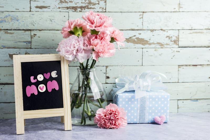 桃红色康乃馨的母亲节概念在清楚的瓶开花 免版税库存图片