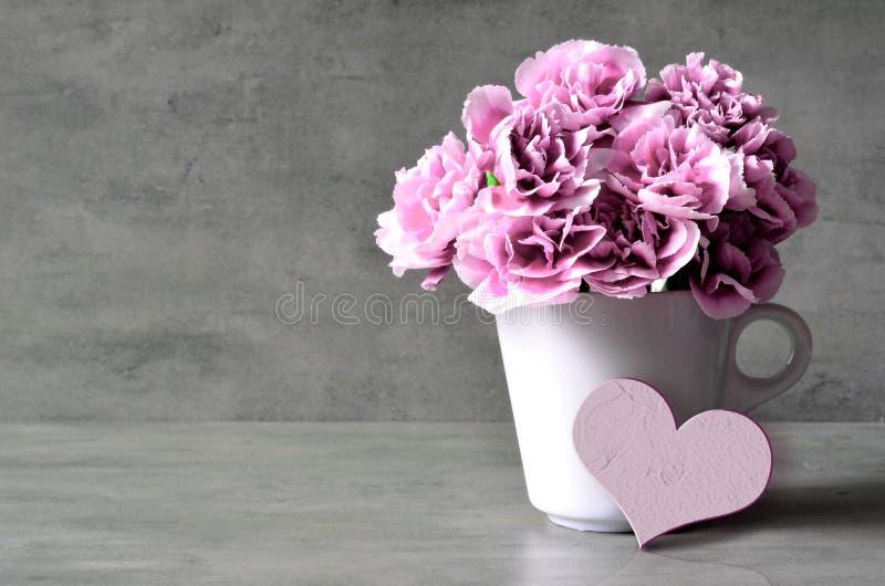 桃红色康乃馨花在杯子和心脏在灰色背景 免版税库存图片