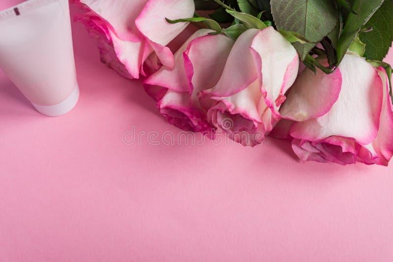 桃红色开花的玫瑰和在粉红彩笔背景的面霜 浪漫skincare花卉框架 r 图库摄影