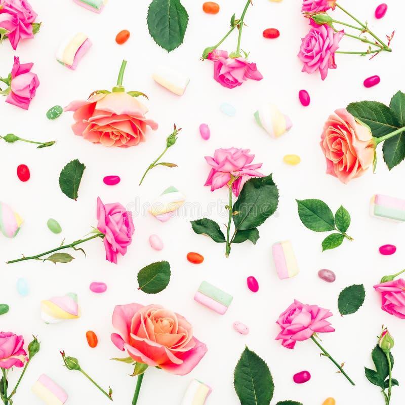 桃红色或橙色玫瑰花和蛋白软糖用五颜六色的糖果在白色背景 平的位置,顶视图 节假日背景 库存例证
