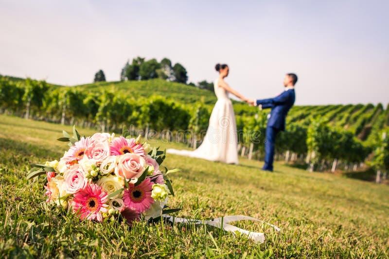 桃红色新娘花束和最近婚姻握在模糊的B的手 免版税库存照片