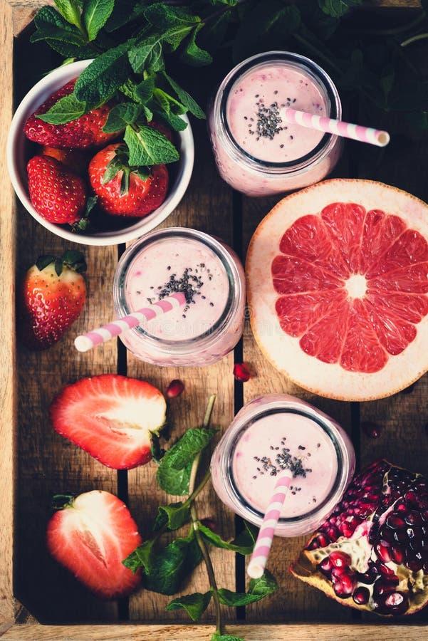 桃红色新鲜的圆滑的人用葡萄柚、草莓和石榴在木盘子,顶视图,选择聚焦,被定调子的图象 库存图片