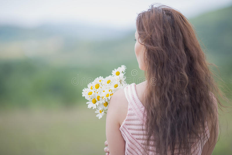 桃红色无袖的礼服的女孩有春黄菊花束的  免版税库存照片