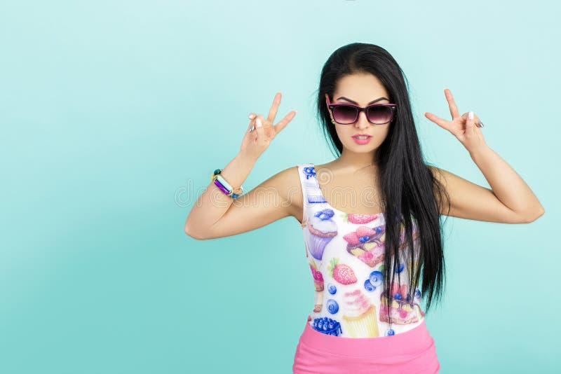 桃红色无袖衫的深色的妇女在蓝色背景 显示两个手指或胜利姿态的太阳镜的女孩 免版税库存图片