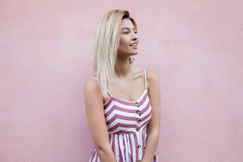 桃红色时兴的镶边sundress的美国俏丽的年轻白肤金发的妇女与在葡萄酒桃红色墙壁附近的一个正面微笑立场 库存图片