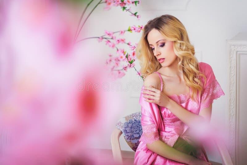 桃红色晨衣的白肤金发的美丽的妇女 免版税库存图片