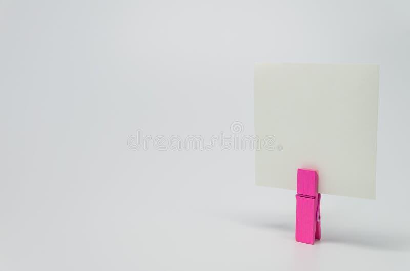 桃红色木夹子夹紧的备忘录纸张有白色背景和选择聚焦 免版税图库摄影