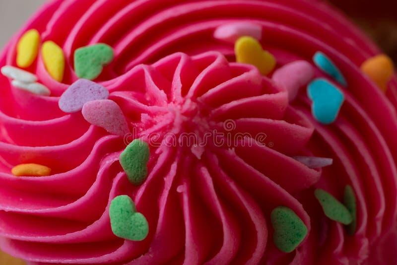 桃红色杯形蛋糕与洒 免版税库存图片