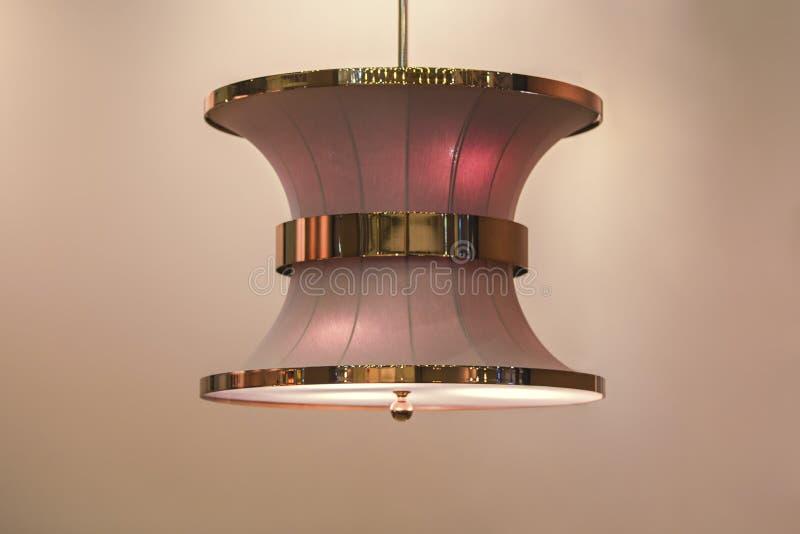 桃红色树荫的一个有趣的形式的时髦的枝形吊灯与金和铜在米黄背景隔绝的装饰元素的 免版税图库摄影
