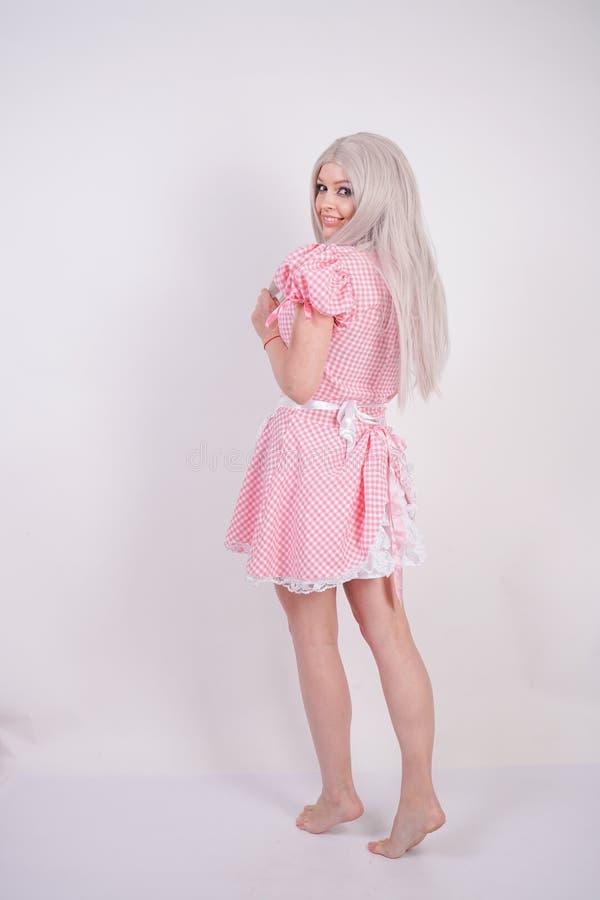 桃红色格子花呢披肩巴法力亚礼服的逗人喜爱的年轻白种人青少年的女孩有摆在白色演播室坚实背景的围裙的 免版税库存图片
