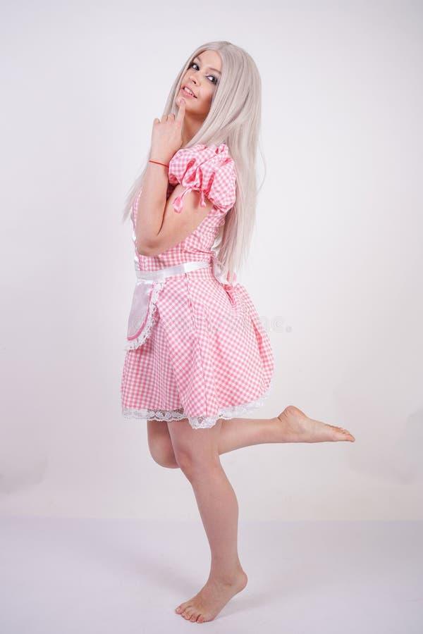 桃红色格子花呢披肩巴法力亚礼服的逗人喜爱的年轻白种人青少年的女孩有摆在白色演播室坚实背景的围裙的 免版税库存照片