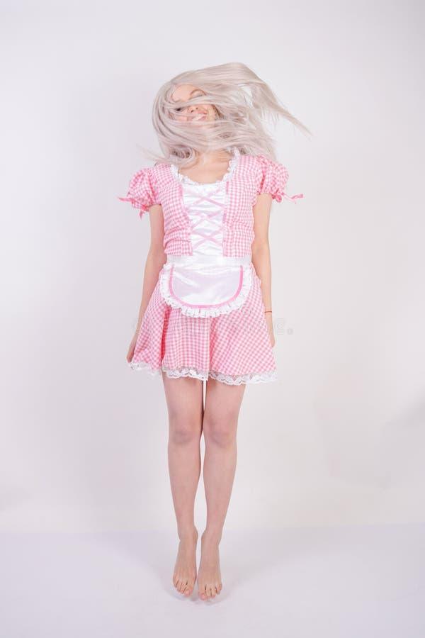 桃红色格子花呢披肩巴法力亚礼服的逗人喜爱的年轻白种人青少年的女孩有摆在白色演播室坚实背景的围裙的 图库摄影