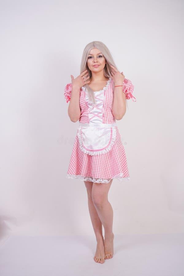 桃红色格子花呢披肩巴法力亚礼服的逗人喜爱的年轻白种人青少年的女孩有摆在白色演播室坚实背景的围裙的 免版税图库摄影
