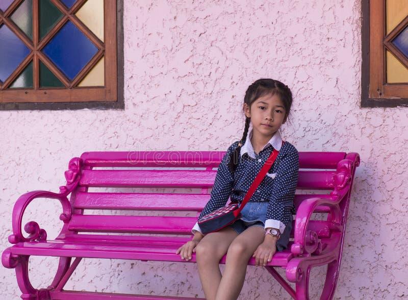 桃红色椅子的小亚裔女孩 库存照片