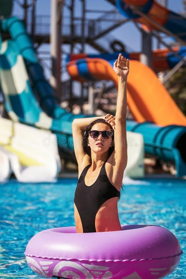 桃红色橡胶环的妇女在游泳场 库存照片