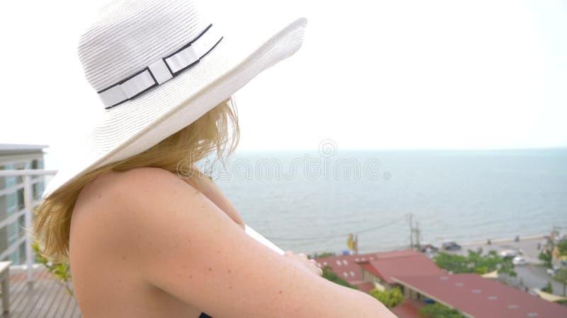 桃红色比基尼泳装的一名妇女由在屋顶的水池享受海视图 库存照片