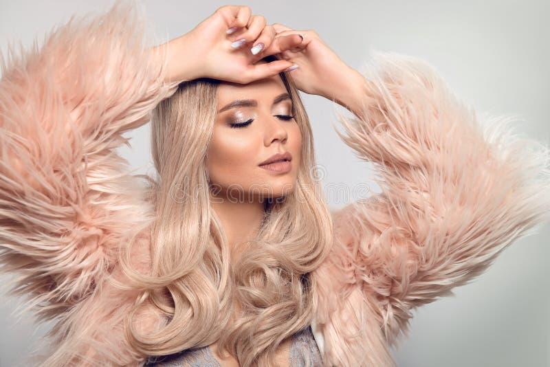 桃红色毛皮caot的美丽的年轻白肤金发的妇女 冬天时尚 有长的卷曲发光的头发和构成的秀丽性感的式样女孩 免版税图库摄影