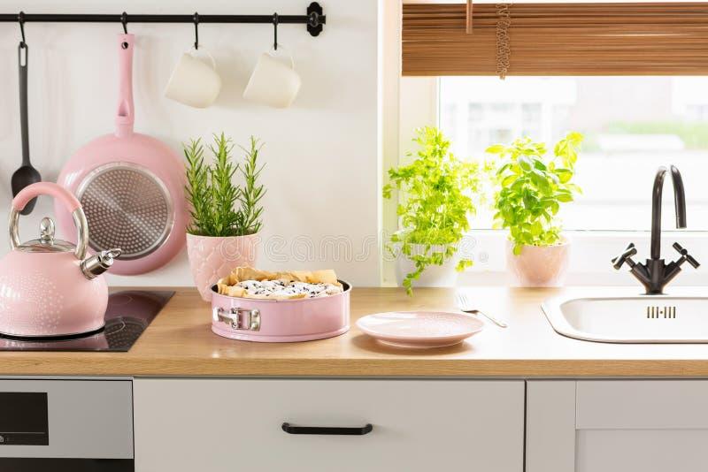 桃红色水壶和蛋糕在木工作台面在明亮的厨房inte 库存照片