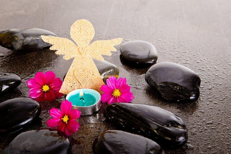 桃红色波斯菊花、蓝色tealight蜡烛和粗麻布天使塑造 免版税库存照片