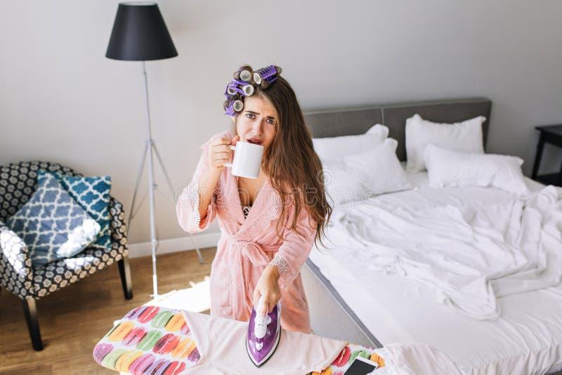 桃红色浴巾的美丽的主妇有卷发的人的在家在电烙的衣裳 喝茶的她,看起来疲乏对照相机 免版税库存图片