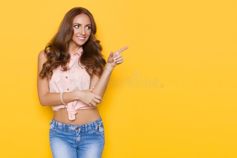 桃红色淡色衬衣的美丽的少妇指向 免版税库存照片