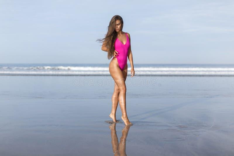 桃红色游泳衣的美丽的女孩在蓝色海洋在黎明 免版税库存照片