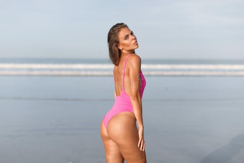 桃红色游泳衣的美丽的女孩在蓝色海洋在黎明 库存图片