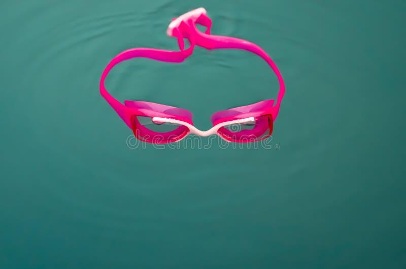 桃红色游泳风镜特写镜头在水中 免版税库存照片