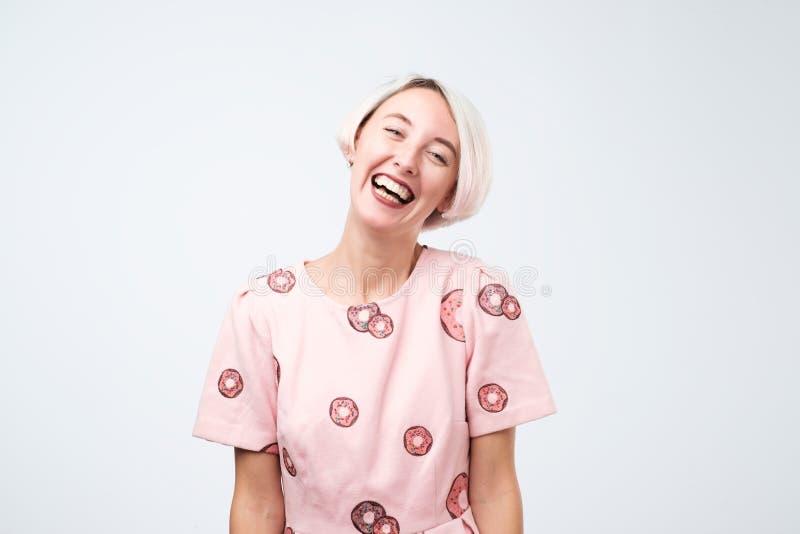 桃红色滑稽的礼服的笑的少妇有好正面心情 库存照片