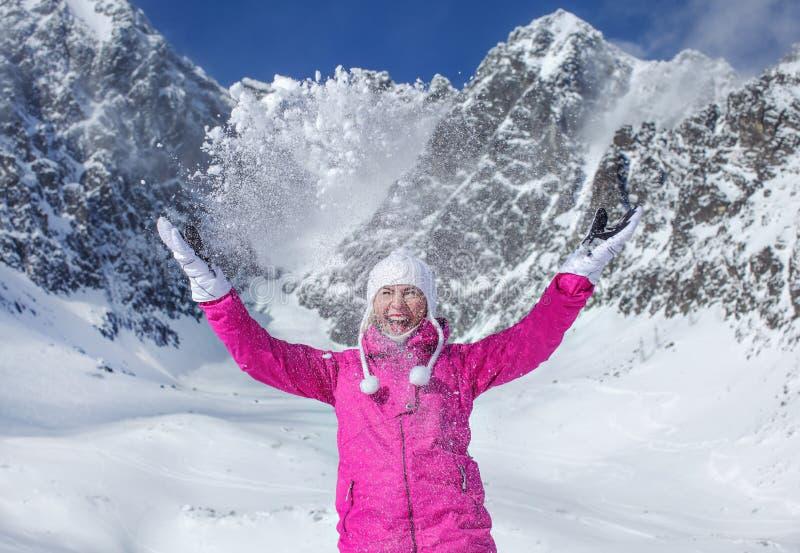 桃红色滑雪夹克衫、手套和冬天帽子的年轻女人,微笑,投掷的雪在天空中,发光在她后的山的太阳 免版税库存图片