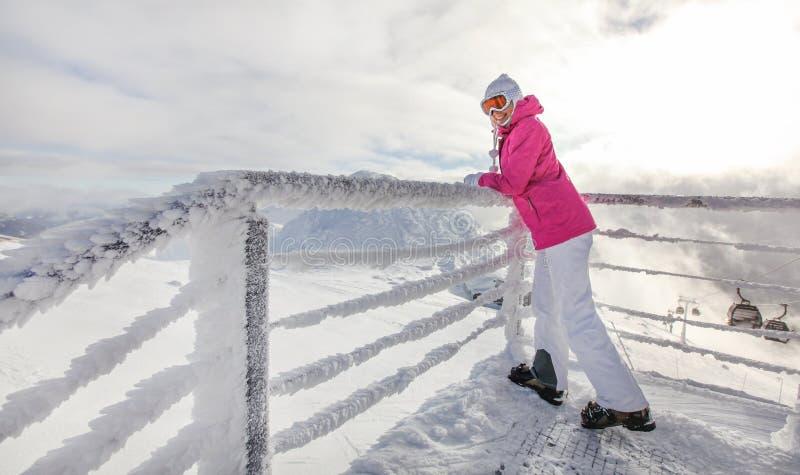 桃红色滑雪夹克衫、起动手套倾斜在水晶积雪的栏杆的帽子和风镜的年轻女人,回顾 太阳发光 库存照片