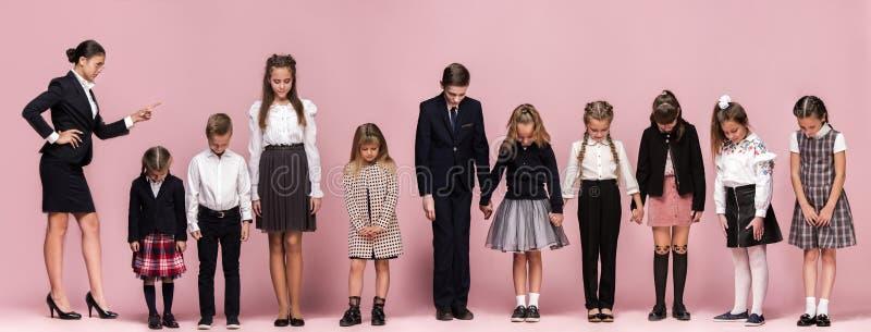 桃红色演播室背景的逗人喜爱的时髦的孩子 一起站立美丽的青少年的女孩和的男孩 库存图片
